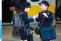 Kleiner japanischer Student wartete auf einen Zug zur Schule Stockbilder