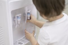 Kleiner Junge übergibt das Erhalten des Wassers von einer Kühlvorrichtung in einer Schule oder in einem Kindergarten stockbild