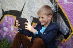 Kleiner Junge absorbiert in seine Tablette für die Erziehung und das Spielen stockfoto