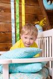 Kleiner Junge auf Bank mit Kissen zuhause Stockfotos