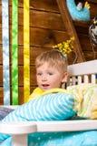Kleiner Junge auf Bank mit Kissen zuhause Lizenzfreies Stockfoto
