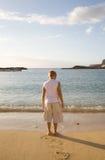 Kleiner Junge auf dem Strand, der unten schaut Stockfotos