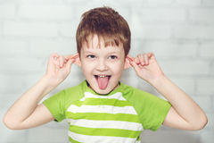 Kleiner Junge, auf den Ohren ziehend Stockfotos