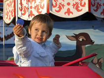Kleiner Junge auf einem Merry-go-round Stockfoto