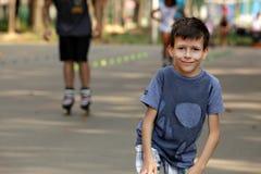 Kleiner Junge auf Hintergrundrollschuhkindern stockbilder