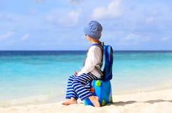 Kleiner Junge auf Strand mit Koffer, Kinder reisen stockfotos