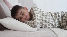 Kleiner Junge beim Pyjamalügen schlafend auf dem Bett stock footage