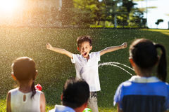 Kleiner Junge Bestrafung, damit Wasserwerferspray Körper nassmacht Stockbild