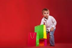 Kleiner Junge blickt in Pakete mit Geschenken auf einem roten Hintergrund lizenzfreies stockbild