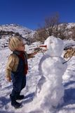 Kleiner Junge, das blonde Haar, spielend im Winter mit Schnee, errichtet Schneemann Tragende Jeans und Schal Stockbilder