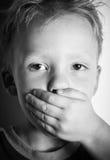 Kleiner Junge deckte seinen Mund mit seiner Hand ab. Stockbild