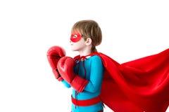 Kleiner Junge in den Boxhandschuhen und im Klagensuperhelden lokalisiert auf einem weißen Hintergrund lizenzfreies stockfoto