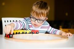 Kleiner Junge in den Gläsern mit der Syndromdämmerung, die mit hölzernen Eisenbahnen spielt stockbild