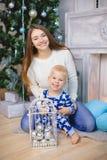 Kleiner Junge in den Pyjamas sitzen und lächeln mit seiner Schwester nahe Weihnachtsbaum Stockbilder