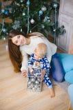 Kleiner Junge in den Pyjamas sitzen und lächeln mit seiner Schwester nahe Weihnachtsbaum Stockfoto
