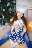 Kleiner Junge in den Pyjamas und Weihnachtsmann-Hut sitzen Lächeln mit seiner Schwester nahe Weihnachtsbaum Zeigen Sie Frieden Lizenzfreie Stockbilder