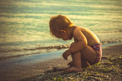 Kleiner Junge in den roten kurzen Hosen spielte auf dem Strand Stockfotos