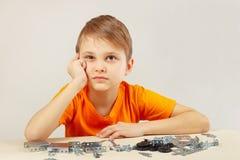 Kleiner Junge denkt, das vom mechanischen Erbauer zusammenbauen Lizenzfreie Stockfotos