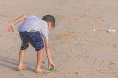 Kleiner Junge, der Abfall auf dem Strand für sauberes hohes umweltsmäßigkonzept aufräumt lizenzfreie stockbilder