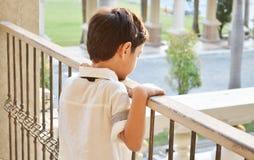 Kleiner Junge, der allein am Balkon steht lizenzfreie stockfotos