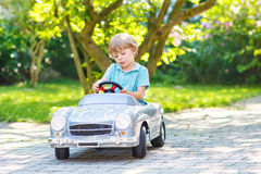 Kleiner Junge, der altes Auto des großen Spielzeugs, draußen fährt Stockbild