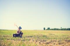 Kleiner Junge, der auf altem Koffer mit Insektnetz sitzt Stockfoto