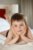 Kleiner Junge, der auf Bett legt Stockbild