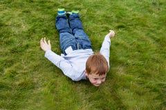 Kleiner Junge, der auf das Gras in gleitender Haltung legt Stockfotografie
