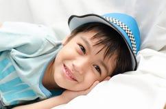 Kleiner Junge, der auf das Sofa betrachtet Kamera legt Lizenzfreie Stockfotos