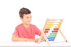 Kleiner Junge, der auf dem Abakus gesetzt an einem Tisch zählt Stockfoto