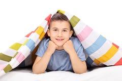 Kleiner Junge, der auf dem Bett bedeckt mit einer Decke liegt Lizenzfreie Stockfotos
