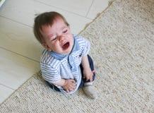 Kleiner Junge, der auf dem Boden, ihm ` s Umkippen und dem Schreien sitzt Das chil Lizenzfreie Stockfotos