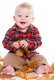 Kleiner Junge, der auf dem Boden mit Ahornblättern spielt Stockfotografie