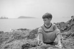 Kleiner Junge, der auf dem Felsen auf dem Strandgesichtsblick glücklich sitzt Lizenzfreie Stockfotos