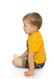 Kleiner Junge, der auf dem Fußboden sitzt Stockbild