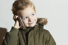 Kleiner Junge, der auf dem Mobiltelefon spricht modernes Kind im Wintermantel Kinder in der erwachsenen Kleidung Kinder Stockfoto