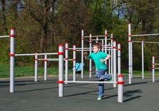 Kleiner Junge, der auf dem Spielplatz läuft Stockfoto