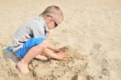 Kleiner Junge, der auf dem Strand im Sand spielt Stockfoto