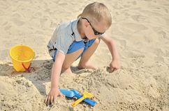 Kleiner Junge, der auf dem Strand im Sand spielt Stockfotografie