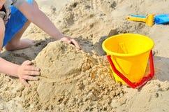 Kleiner Junge, der auf dem Strand im Sand spielt Kind sculpts Zahlen aus dem Sand heraus Lizenzfreie Stockbilder