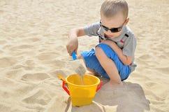 Kleiner Junge, der auf dem Strand im Sand spielt Kind sculpts Zahlen aus dem Sand heraus Tätigkeiten im Sommer auf dem Meer Lizenzfreies Stockbild