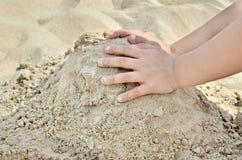 Kleiner Junge, der auf dem Strand im Sand spielt Kind sculpts Zahlen aus dem Sand heraus Tätigkeiten im Sommer auf dem Meer Lizenzfreies Stockfoto