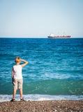 Kleiner Junge, der auf dem Strand sitzt und auf dem Schiff schaut. Stockfoto