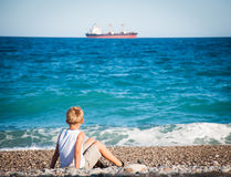 Kleiner Junge, der auf dem Strand sitzt und auf dem Schiff schaut. Stockbilder