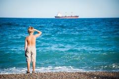 Kleiner Junge, der auf dem Strand steht und auf dem Schiff schaut. Stockfoto