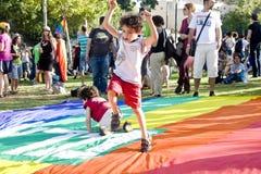 Kleiner Junge, der auf der Regenbogenmarkierungsfahne spielt Lizenzfreies Stockfoto