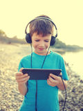 Kleiner Junge, der auf der Tablettenweinlese im Freien spielt lizenzfreie stockbilder