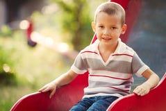 Kleiner Junge, der auf einem Dia in einem Kinderspielplatz spielt Lizenzfreie Stockfotografie