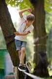 Kleiner Junge, der auf einem Drahtseil balanciert Stockfotos