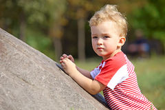 Kleiner Junge, der auf einem Felsen im Park sich lehnt Lizenzfreies Stockbild